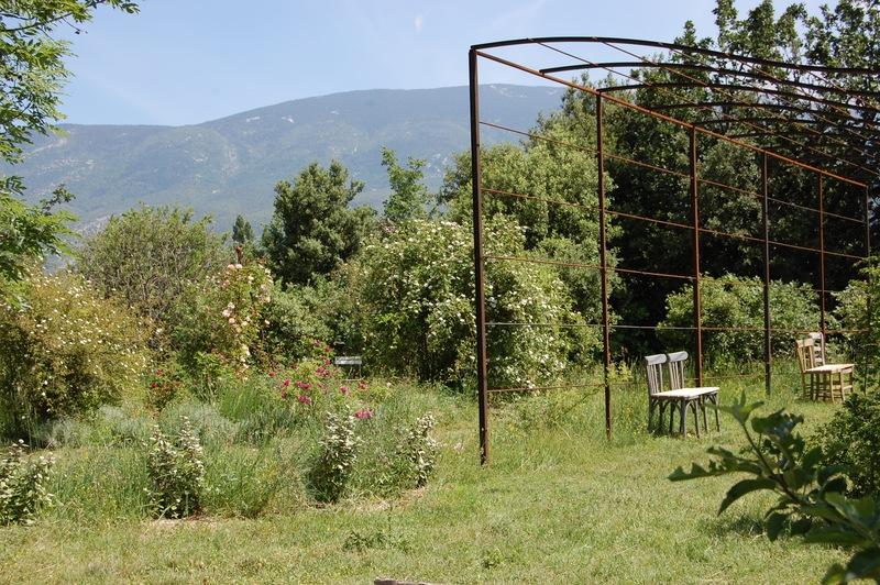 """Les bancs-chaises sous la pergola et la vue sur le massif """"Le carré d'Héléne"""" avec le Ventoux en fond. Paysage à la roseraie de Gérenton à Bédoin."""